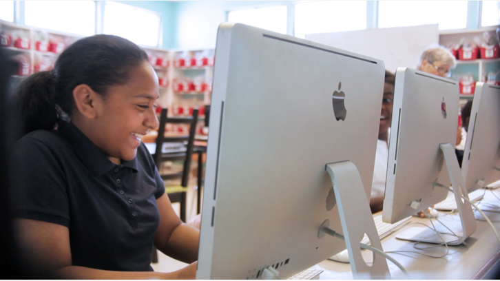 Girl plays CodeCombat on a computer while smiling