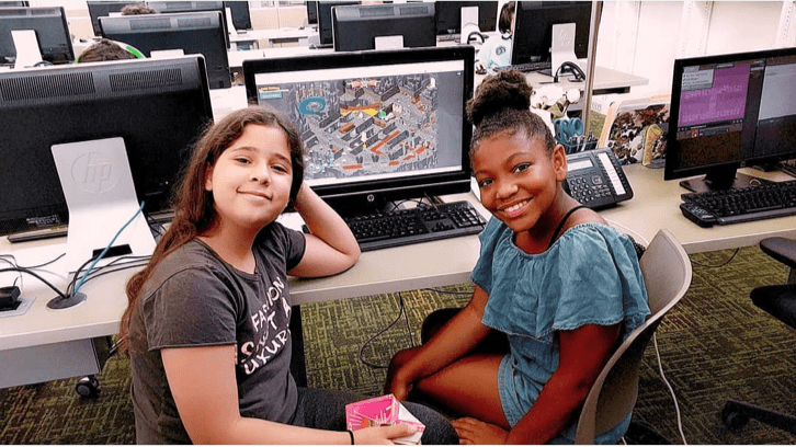 Two girls share a computer with CodeCombat playing between them
